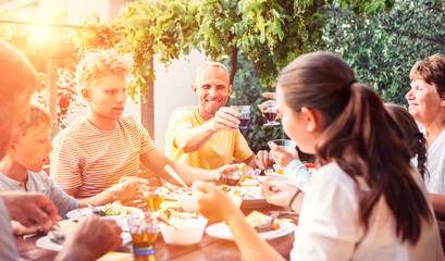 Big family have a dinner on open air in summer garden