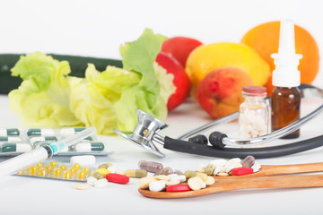 Pills and vitamins supplement, madicine therapy. Fresh fruits and vegetables in background. Health and wellness concept.