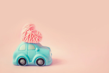Miniature toy blue car delivering pink thread heart for Valentine's day against pink background. Love, romance, Valentines day concept. Selective focus