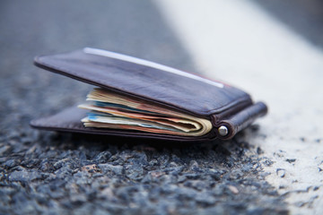 Wallet with money on the road. Wasted time is money lost concept.