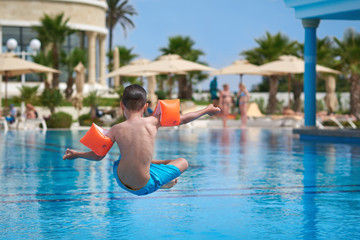 Caucasian boy in floating sleeves jumping into water in swimming pool at resort. Back view.