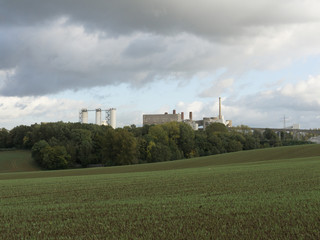 A large modern plant among the forest and green fields outside the city