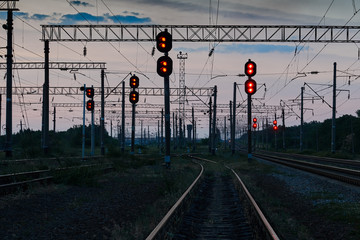railroad traffic lights and infrastructure during beautiful sunset, colorful sky, transportation and industrial concept