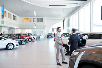 Professional salesperson selling new cars in a modern auto salon. Two men standing and choosing a new car Wall mural