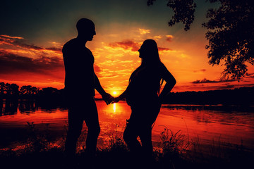 silhouette of a man and a pregnant woman against the background of a river and sunset. A loving couple holding hands