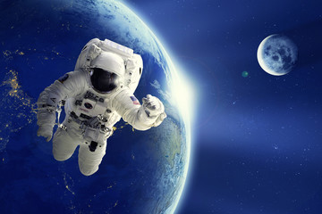Astronaut or Spaceman floating in space with Earth planet and moon background. Element of this image provided by NASA