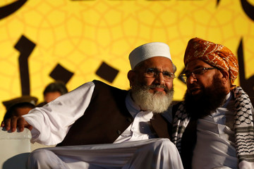 Siraj ul Haq (L) leader of MMA a coalition between religious-political parties, listens to Maulana Abdul Ghafoor Haideri, as they are attend a campaign rally, ahead of general elections in Karachi