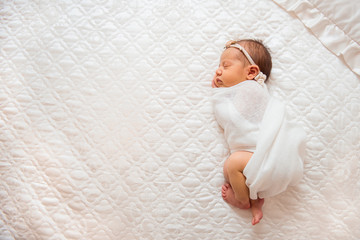 Cute newborn baby is sleeping on a big bed. Copy space and top view