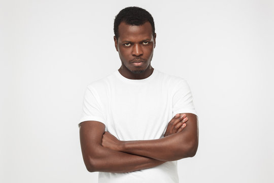 Indoor picture of young handsome African American man pictured against gray background wearing white T-shirt standing with crossed arms and serious face expression ready to cope with problems