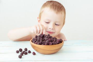 Cute little boy gently takes blackberries in his hand