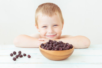 Smiling baby boy and a plate of ripe blackberries on the table