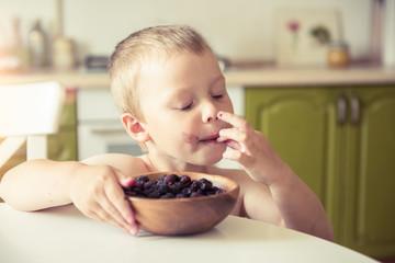 Funny dirty little boy eats blackberries in the kitchen