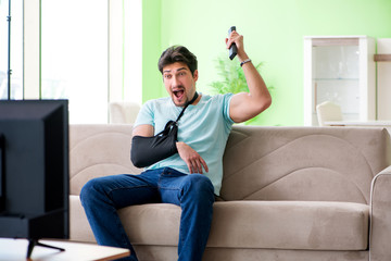 Arm injured man sitting on the sofa watching tv