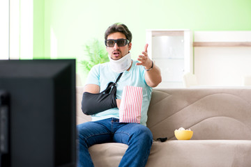Man with neck and arm injury watching tv