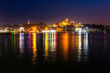 Night view of Istanbul. Panorama cityscape of famous tourist destination Golden Horn bay part of Bosphorus strait. Travel illuminated landscape Bosporus, Turkey, Europe and Asia.