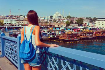Young tourist woman on Galata bridge, Golden Horn bay, Istanbul. Panorama cityscape of famous tourist destination Bosphorus strait channel. Travel landscape Bosporus, Turkey, Europe and Asia.