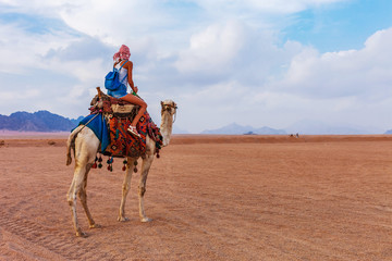 Tourist woman in traditional arabian clothes with camel in the Sinai Desert, Sharm el Sheikh, Sinai Peninsula, Egypt.