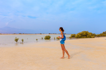 Tourist woman at the Red Sea coast and mangroves in the Ras Mohammed National Park. Famous travel destionation in desert. Sharm el Sheik, Sinai Peninsula, Egypt.