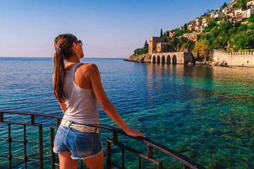 Young woman look on ancient shipyard from Kizil Kule tower in Alanya peninsula, Antalya district, Turkey, Asia. Famous tourist destination high mountains. Part of ancient old Castle. Summer bright day