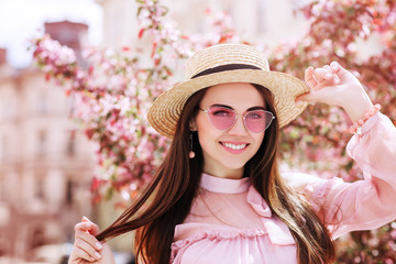 Outdoor close up portrait of young beautiful happy smiling woman wearing stylish pink cat eye sunglasses, straw hat, earrings, blouse, posing in street of city. Copy, empty space for text