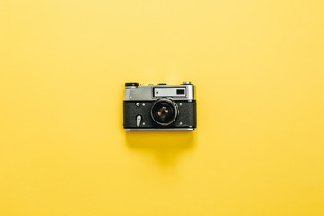 Vintage retro camera on yellow background. Flat lay, top view.
