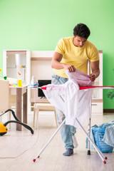Leg injured man doing clothing ironing at home