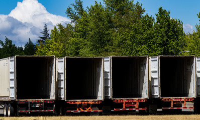 Semi tractor trailers empty and open parked in a lot with trees