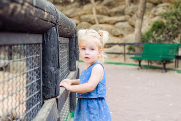 Portrait of cute little blondy toddler girl looking at camera and leaning on a wooden fence in the zoo or city park Child safety concept. Selective focus. Copy space.
