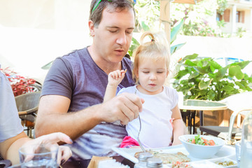 Adult Father feeding his cute toddler daughter during family breakfast in outside cafe. Family rest, spending time together concept. Family traditions. Selective focus. Copy space.