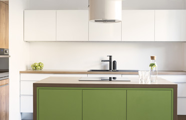 Modern and design scandinavian space with kitchen island, table and accessories. Sunny and bright kitchen with white white wall. Stylish accessories.