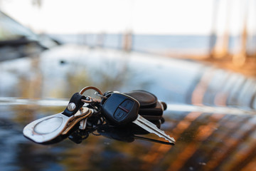 Keys with immobilizer on the hood of the car against the window. Beautiful summer light and sun. The hood reflects the sunset and the sun's rays with the scenery of nature