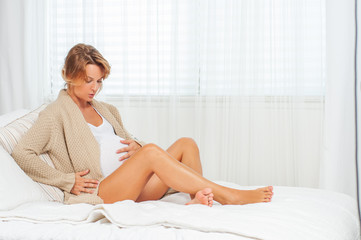 Happy pregnant woman touching her belly is sitting on bed