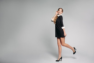 Smiling beautiful and positivity woman with curly hairstyle wearing in fashionable black dress jumping up in studio and looking at camera. Stylish woman dancing, posing. Shopping, style concept.