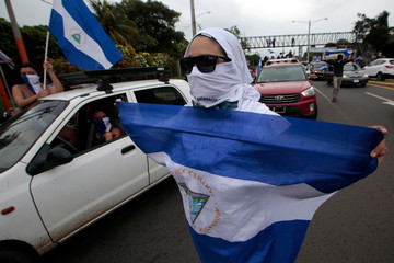 An anti-government protester takes part in a caravan of car and motorcycles to demand an end to violence in Ticuantepe