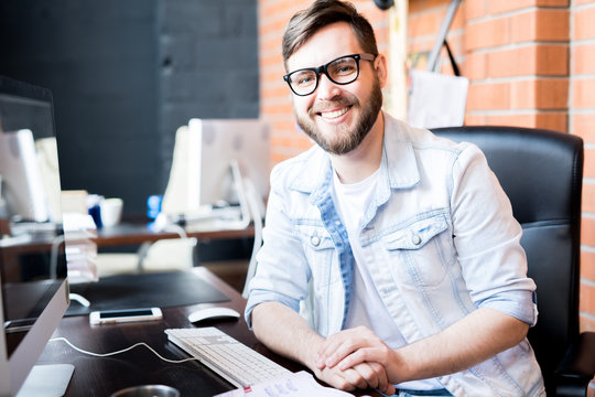 Portrait of contemporary business manager wearing casual clothes smiling happily at camera while sitting at computer desk in modern office