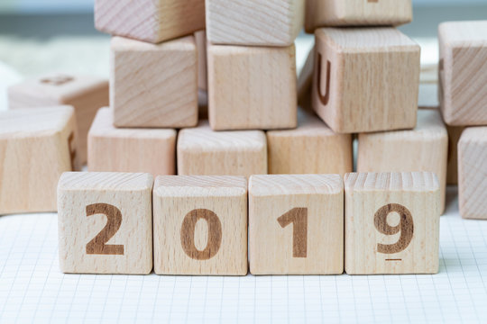 New year 2019, review or resolution concept, cube wooden block with alphabet building the numbers 2019 on grid line notebooks with other random block in the background