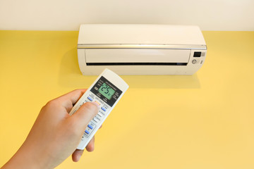 Hand turning on home air conditioning