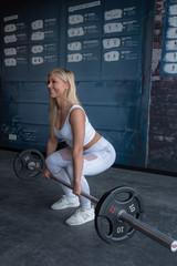 Blonde Frau trainiert Cross Fit im Fitness Studio