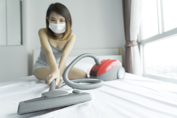 woman using vacuum cleaner while cleaning white bed at home.Beautiful young Asian girl cleaning bed in house. Female people lifestyle, maid housewife work concept.