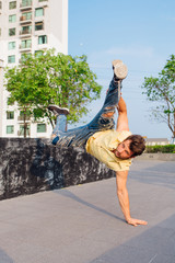 Young man dancing breakdance on the street. Man stands on hands.
