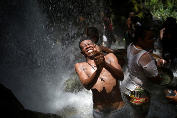 Pilgrim takes a bath during the celebration of the annual pilgrimage to the waterfall in Saut D'Eau