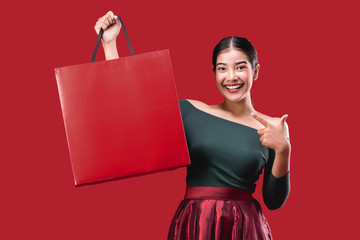 portrait of happy young cute woman posing with shopping bags over Red background.