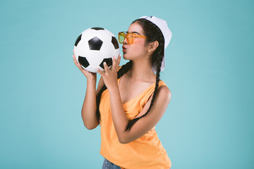beautiful young woman kissing a football on Blue background.