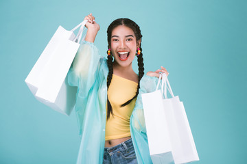 Happy young woman in raincoat with shopping bags,shopping in rainy day sale concept,over blue background.