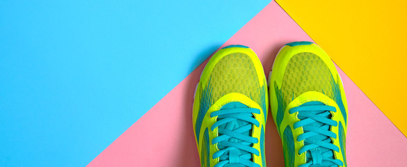 Pair of sport shoes on colorful background. New sneakers on pink, blue and yellow pastel background, copy space. Overhead shot of running shoes. Top view, flat lay