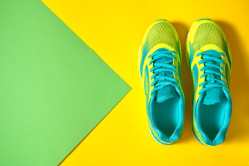 Pair of sport shoes on colorful background. New sneakers on yellow and green pastel background, copy space. Overhead shot of running shoes. Top view, flat lay