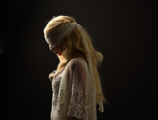 portrait of blonde girl wearing a white lace dress and blindfold.  black studio background.