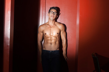 Sexy nerdy guy leaning against wall