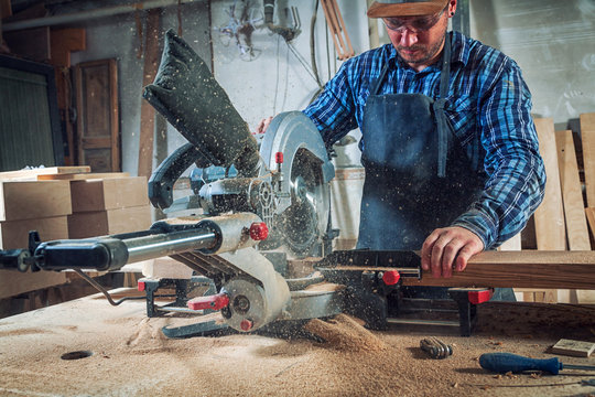 Carpenter work with circular saw for cutting boards, the man sawed bars, construction and home renovation, repair and construction tool