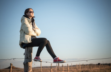 teenage girl in sunglasses sits on a fence and looks at the sunset